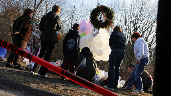 People visit a memorial outside Sandy Hook Elementary School in Newtown, Conn., on Dec. 15.