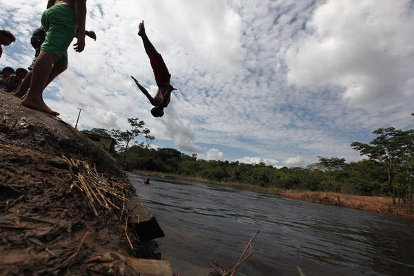 A man flips into a stream leading to the Xingu River. The area is challenged by deforestation; agriculture; mining; a governmental dam building spree; illegal land speculation, including the occupation of forest reserves and indigenous land; and other issues.