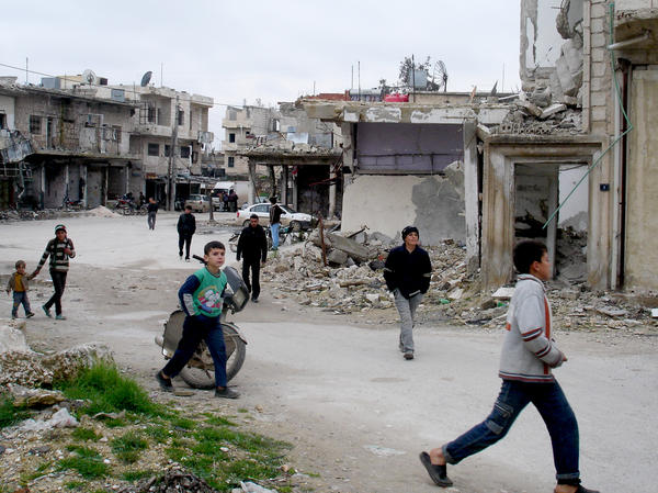 Young boys rush to Kafr Nabl's main square for the weekly Friday protest.