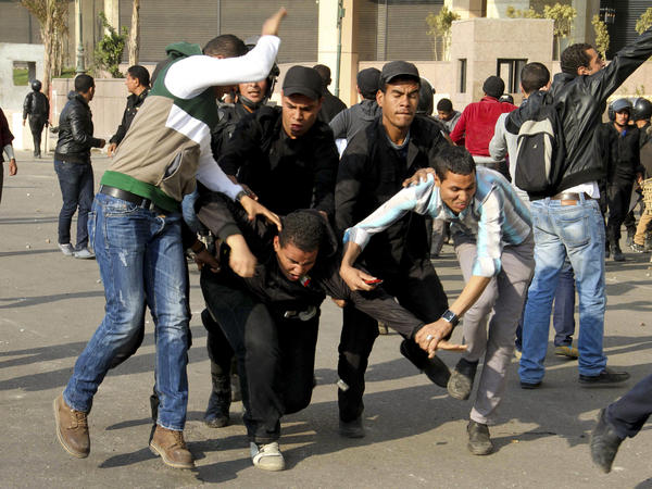 Egyptian policemen arrest an alleged rioter during clashes in Cairo on Wednesday.