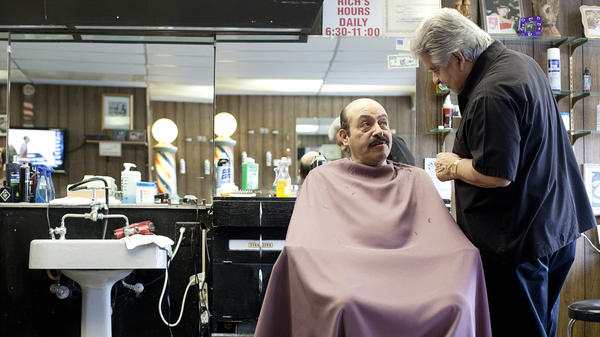 Richard Piña, 69, with customer Augustin Bustos at Rich's Den barbershop in Calumet City, Ill. Piña, who retired from the Chicago police force 12 years ago, works at his shop four or five hours a day.