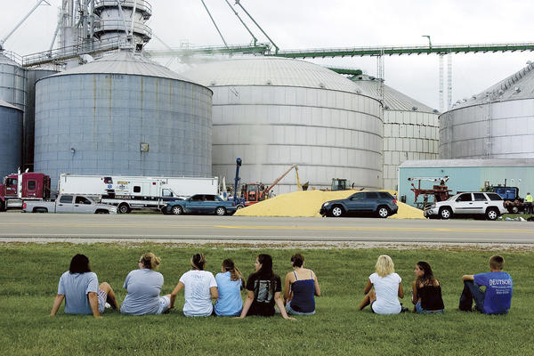Friends and classmates of Wyatt Whitebread, Alex Pacas and Will Piper watch as rescuers work to free the boys from the bin (center) full of thousands of bushels of corn. Only Piper survived.