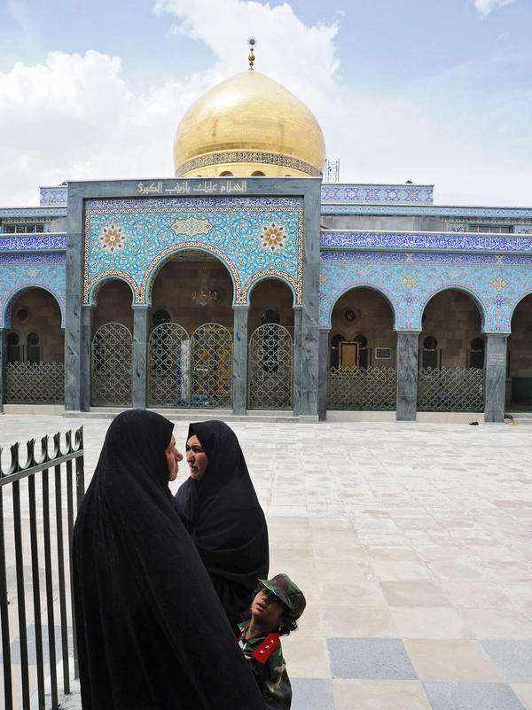 Syrian pilgrims stand in the courtyard of the Sayida Zeinab shrine with a young girl dressed as a Syrian military officer on May 29, 2012, in Damascus.