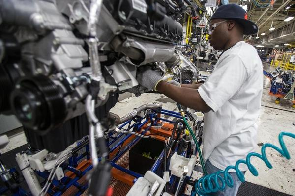 A worker installs parts on a Chrysler SUV engine at the Jefferson North Assembly Plant in Detroit. Plants in the U.S. are now operating above 90 percent capacity, but automakers are wary of adding large numbers of new workers.