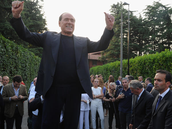 Former Italian Prime Minister Silvio Berlusconi hails his supporters in front of his house, Villa San Martino, on July 1 in Milan.