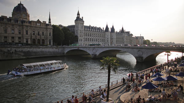"People enjoy the sun next to Pont Neuf bridge as ""Paris Plage, or Paris Beach, opens along the banks of the Seine river in Paris, on July 20. The annual free event brings a half-mile of beach into the heart of the French capital."
