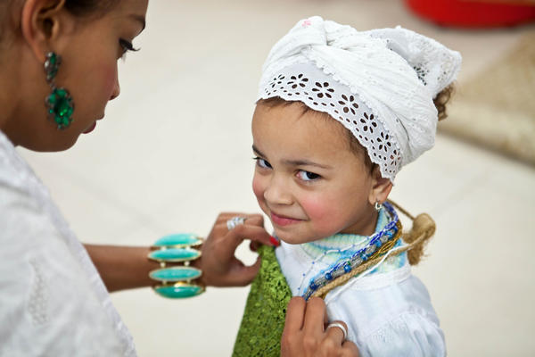A child who is already a CandombléŽ practitioner has her clothes adjusted by an older member of the group. The CandomblŽéŽ faith is accepting more children these days, to secure the future of the religion.