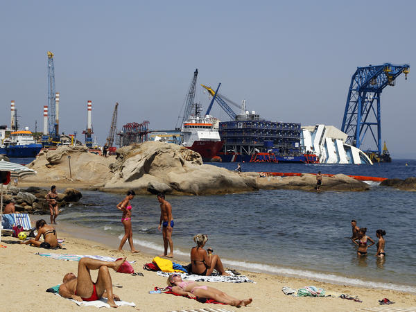 People sunbathe in front of the capsized Costa Concordia outside Giglio harbor, on Aug. 8. The cost of the salvage operation — one of the biggest in history — could exceed $1 billion.