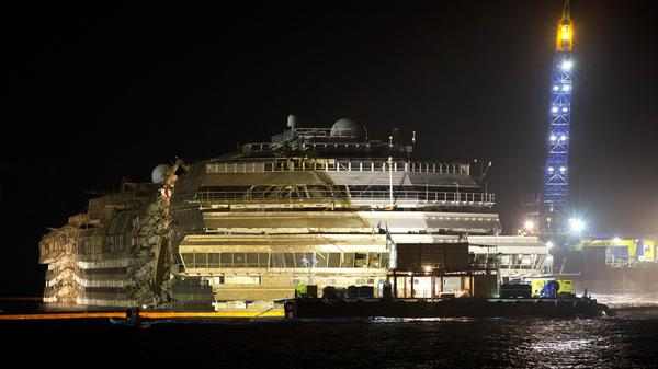 "The Costa Concordia is seen after it was lifted upright on the Tuscan Island of Giglio, Italy, early Tuesday morning. Officials declared the results of the 19-hour operation ""perfect."""