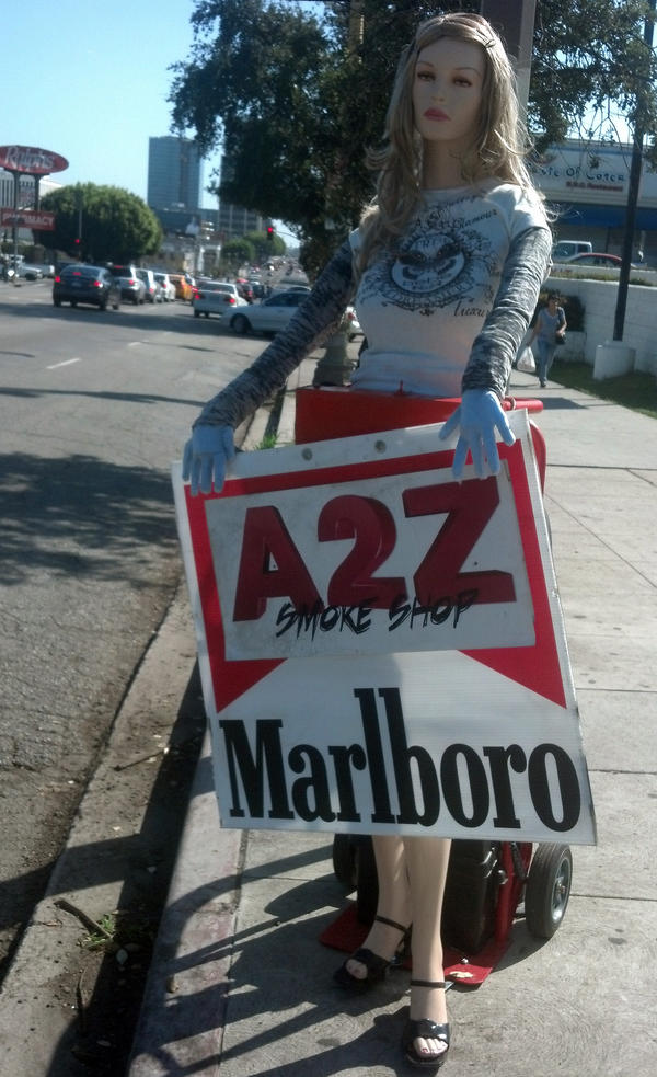 """Sandy,"" a sign-waving mannequin, helps bring in customers to a Los Angeles smoke shop."