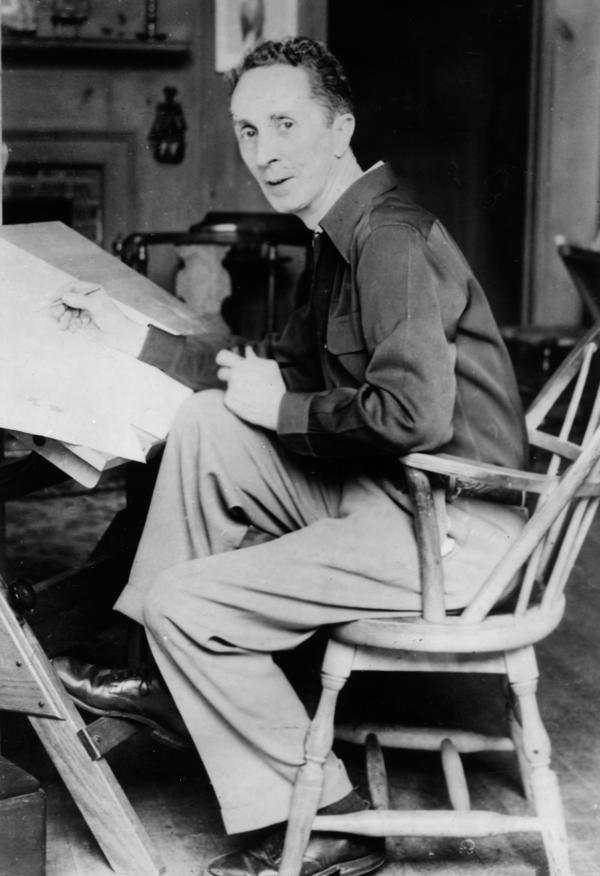 American artist Norman Rockwell (1894-1978) looks up while seated at his drawing table, circa 1945.
