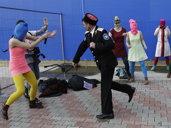 A Cossack militiaman attacks Nadezhda Tolokonnikova and a photographer as she and fellow members of the punk band Pussy Riot, including Maria Alyokhina, center, in the pink balaclava, stage a protest performance in Sochi on Wednesday.