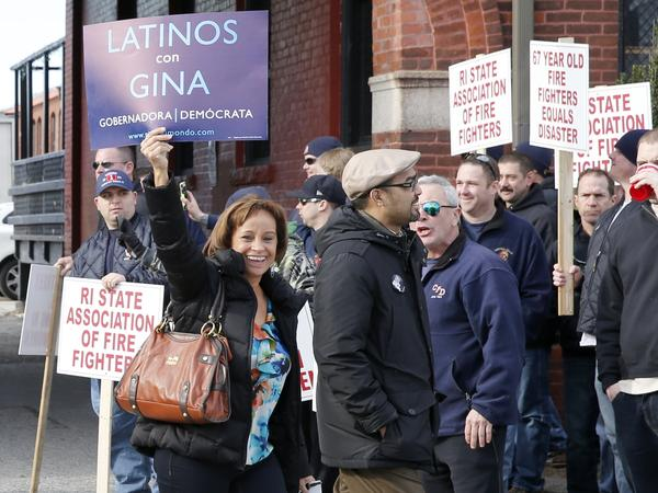Two supporters of gubernatorial candidate Gina Raimondo walk past protesting union members outside a rally at which Raimondo announced her run for the Democratic nomination in Rhode Island in January.