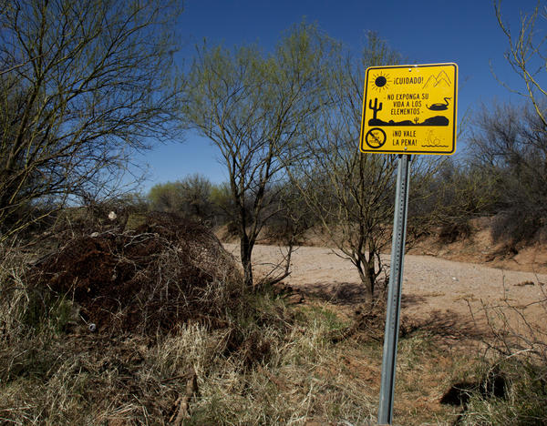 "A sign warns against the many dangers in the desert in Spanish, saying, ""It's not worth it."""