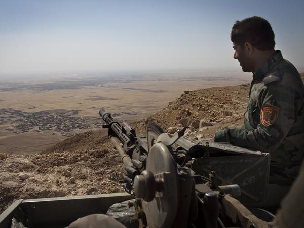 An Iraqi Kurdish Peshmerga fighter hold his position in the mountains east of Mosul.