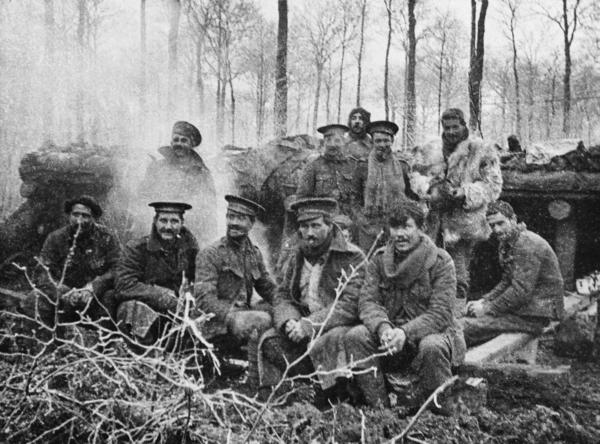 Group of Britain's 1st Battalion London Rifle Brigade just after dinner, at Ploegsteert Wood, Belgium, on Christmas 1914.