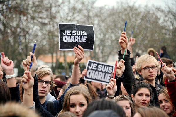 "Students hold pens and signs reading ""I am Charlie"" in La Rochelle, France, on Jan. 8. They were paying tribute to the 12 people killed the day before in an attack on <em>Charlie Hebdo</em> in Paris."