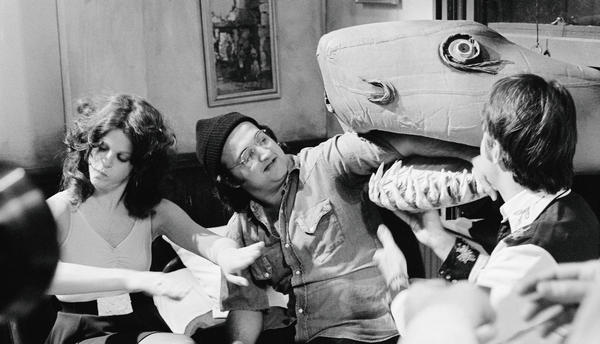 Gilda Radner pays no mind as the Land Shark gobbles John Belushi's arm backstage in 1976.