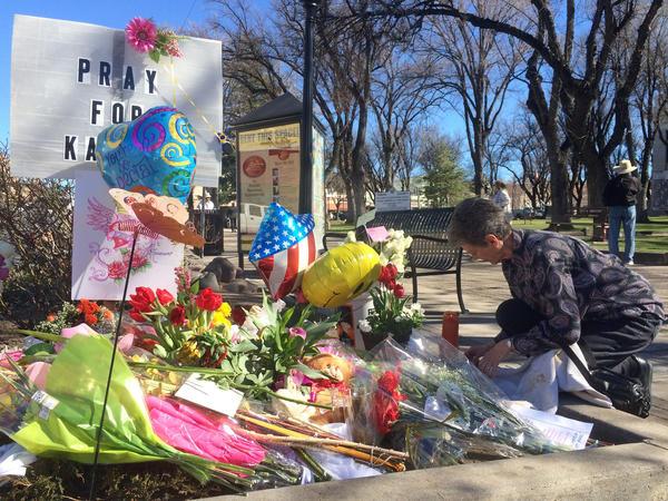 A woman kneels near a makeshift memorial for Kayla Mueller in Prescott, Ariz.
