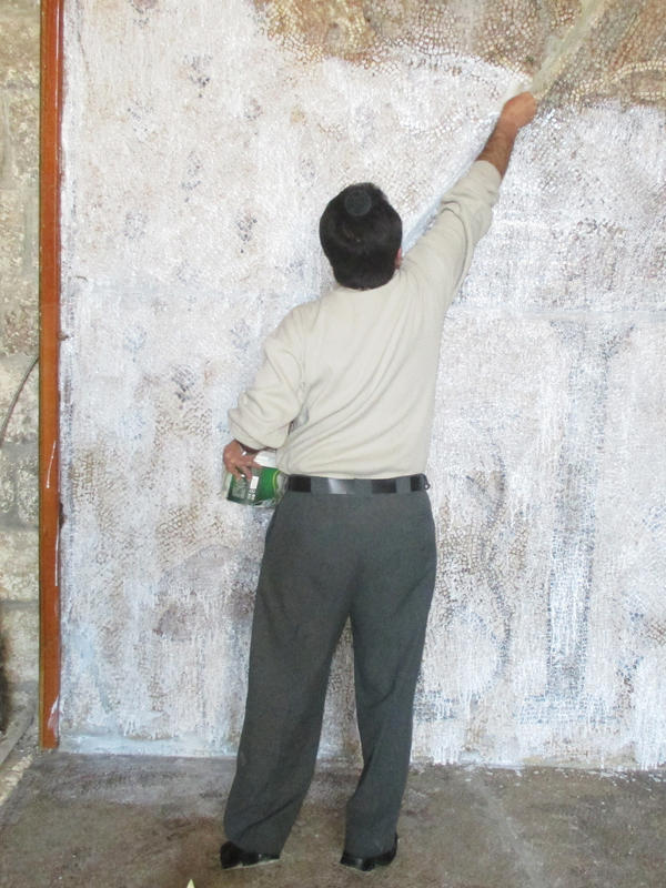Syrian volunteers cover mosaics in the Ma'arra museum with a protective layer of glue, covered by cloth.
