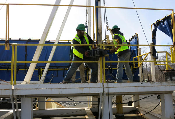 """Students at the Pennsylvania College of Technology are learning a technique called """"tripping pipe,"""" moving a pipe from a stack into a horizontal position and lowering it down into a well.  The students train on a practice drilling rig to learn how to be roustabouts."""