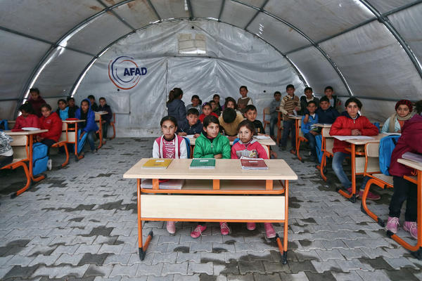 Syrian children listen to a teacher during a lesson in a temporary classroom in Suruc refugee camp on March 25 in Suruc, Turkey. The camp is the largest of its kind in Turkey with a population of about 35,000 Syrians who have fled the ongoing civil war in their country.