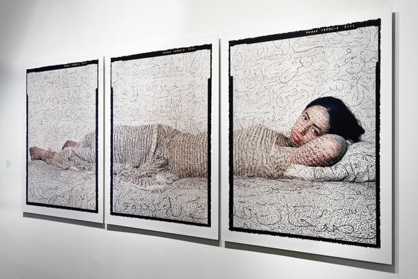 In her 2008 work <em>Reclining Odalisque, </em>Moroccan photographer Lalla Essaydi shows a woman covered in calligraphy.