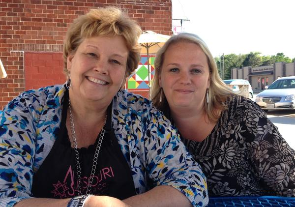 Jenny Doan sits with her daughter Sarah Galbraith, who co-founded Missouri Star Quilt Co., outside two of the new restaurants the company bankrolled in downtown Hamilton, Mo.