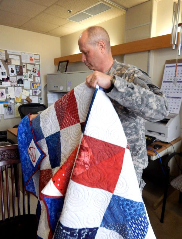Col. Kenneth Trzepkowski, chief of palliative care at Madigan Army Medical Center, unfolds one of the handmade quilts donated to the hospital for the palliative care patients.