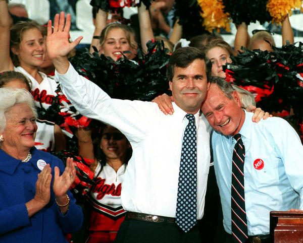 Former President George H.W. Bush embraces his son, Jeb, as Barbara Bush applauds during a rally in downtown Orlando, Fla., in 1994.