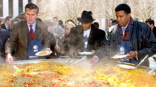 At the Miami-Dade Day festivities in 2002, then-Florida Gov. Jeb Bush (from left) serves helpings of paella with state Rep. Gary Siplin and state Sen. Kendrick Meek.