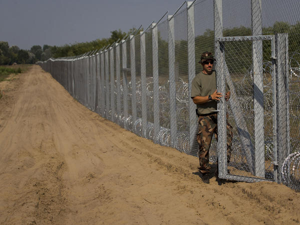 A Hungarian army officer closes the gate of Hungary's new fence on the 110-mile border with Serbia. Hungary's Prime Minister Viktor Orban has taken a number of controversial steps against migrants.