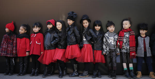 Models for children's wear wait for a show during China Fashion Week in Beijing on Thursday. China announced an end to the one-child policy for urban couples that had been place for more than three decades.