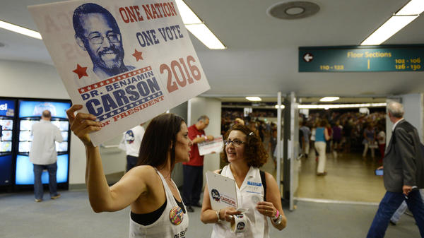 Ben Carson volunteers hold campaign banners and a clipboard as they direct supporters at a rally in Anaheim, Calif.