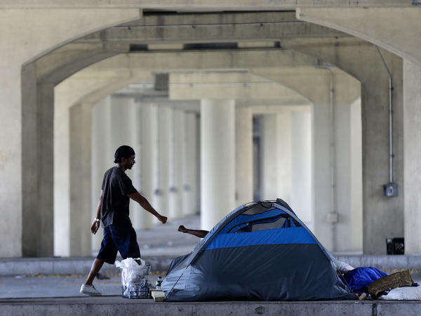Homeless people greet one another under the Pontchartrain Expressway overpass in New Orleans on Aug. 13, 2014. The city health department put up notices that month giving the estimated 150 homeless people 72 hours to leave the area.