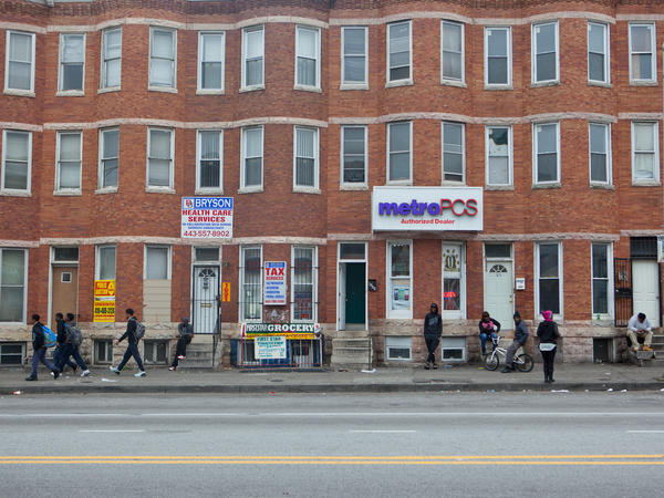 Pedestrians walk on West North Avenue in Baltimore. On Monday, the trial begins for the first of six police officers charged in Freddie Gray's death.