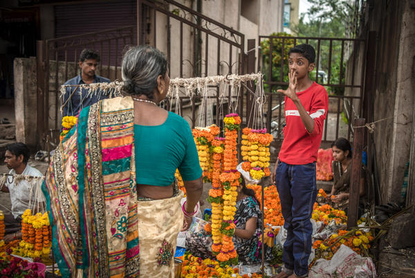 Aniket's favorite part of the day is selling flowers at a street market after school.