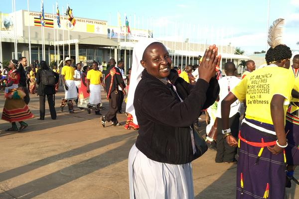 A nun dances in expectation at the Entebbe International Airport in Uganda.