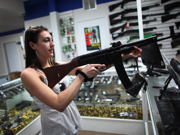 Cristiana Verro looks at guns on sale at the National Armory gun store on April 11, 2013, in Pompano Beach, Fla.