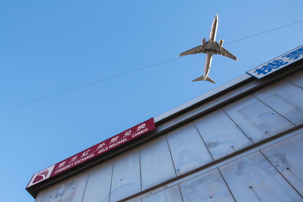 A plane flies over a commercial building in Flushing.