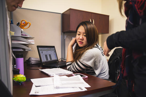 Sabrina Zhang, an administrative assistant at the Flushing YMCA's New Americans Welcome Center, looks over documents with her co-workers. Zhang emigrated from Liaoning province in northeast China and now works closely with immigrants in the community as they settle into life in the United States.