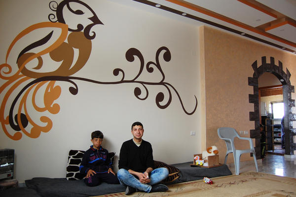Hytham Harara, 21, sits with his little brother<em><strong> </strong></em>in their recently reconstructed home in Gaza City. The family returned home a couple months ago, after a year-and-a-half crammed into a rental.