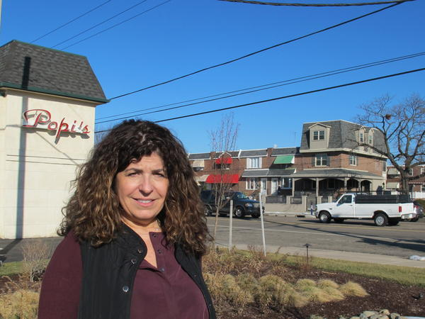 Gina Rucci stands by a new rain garden built in the parking lot of her restaurant in South Philadelphia. The improvements have cut her water runoff bill by 60 percent.