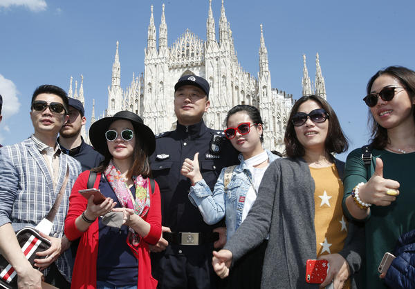 A Chinese police officer poses with Chinese tourists in front of Milan's cathedral on May 3. Chinese police are on patrol with Italian officers to help make Chinese visitors feel safer.