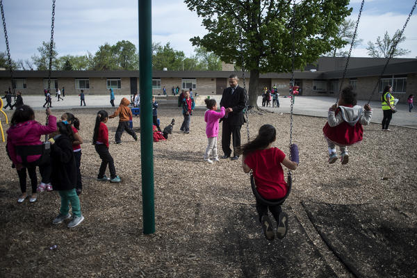 Mel Atkins (center) talks with a Buchanan Elementary School student during recess.
