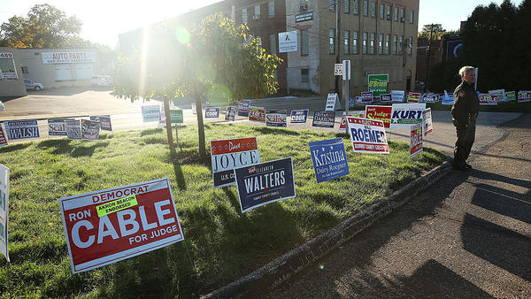Campaign signs are placed outside a polling precinct open for early voting in Akron, Ohio.