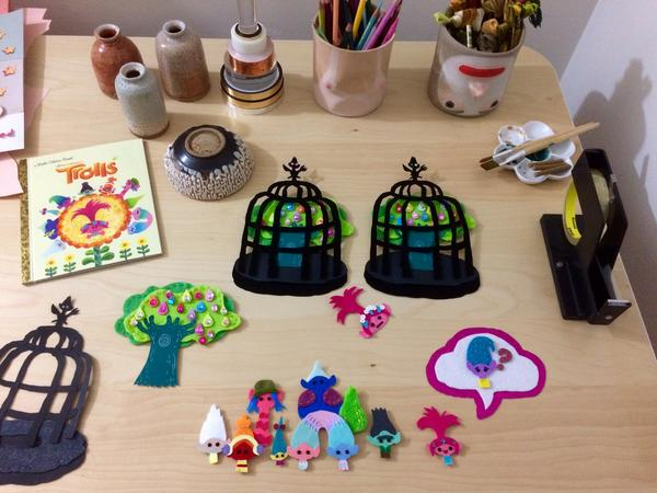 Scrapbook characters and set pieces laid out in Priscilla Wong's studio.