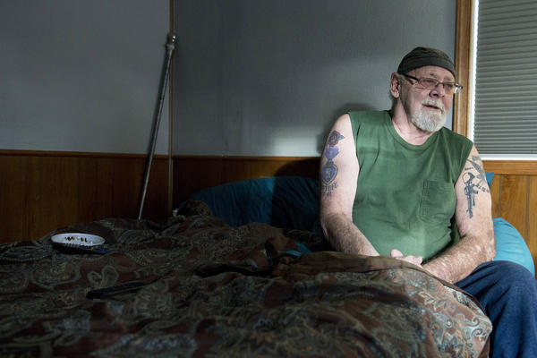 Rusty Welton sits on his bed inside his home. He isn't convinced that a cooperative is the best plan.