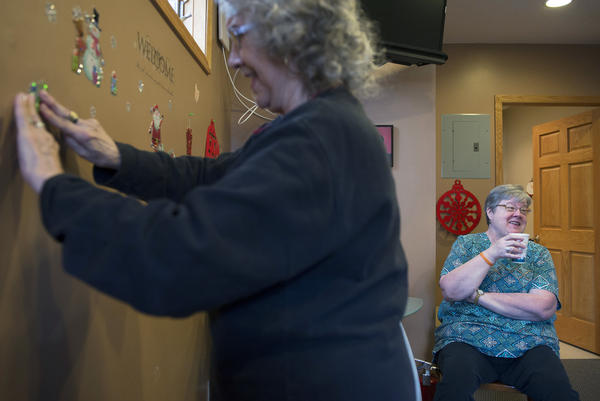 Residents visit in the Park Plaza office as Bonita Johnson (left) hangs a holiday decoration and Pat Streeter sips coffee. Streeter was open to becoming a cooperative, but she felt it was a fractured community.