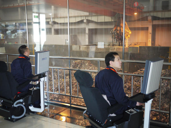 Engineers at Beijing's Gao'antun incinerator power plant control giant claws with joysticks on special chairs inside a cockpit. The claws are capable of lifting eight tons of garbage with each scoop.